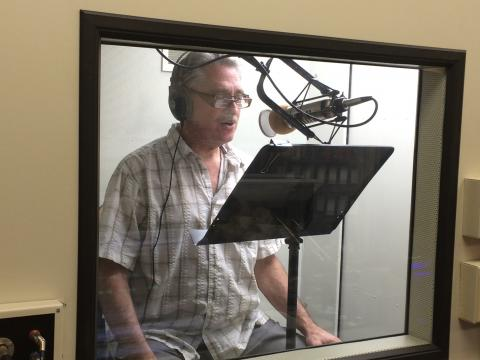 Middle-aged man in a recording booth speaking into a microphone.